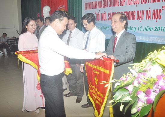 Phòng GD-ĐT Tam Kỳ nhận cờ thi đua xuất sắc của UBND tỉnh do Phó Chủ tịch UBND tỉnh Lê Văn Thanh trao. Ảnh: X.P