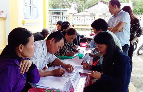 Người dân thôn Phước Châu (Bình Triều) điền trực tiếp vào phiếu đánh giá. Ảnh: Biên Tân