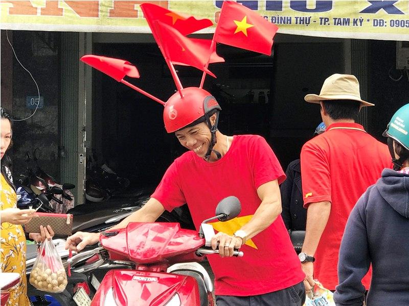 Anh Trương Văn Anh với chiếc mũ bảo hiểm độc đáo, vui vẻ giắc xe máy cho khách. Ảnh: VINH ANH