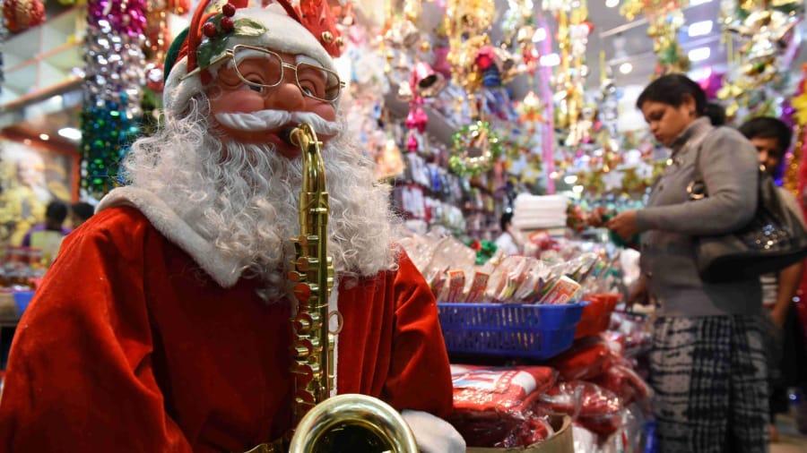 Ông già Noel thổi kèn sacxophone và vật trang trí Gián sinh xuất hiện tại các cửa hàng Ấn Độ, nơi có 28 triệu người trong tổng số hơn 1,2 tỷ người theo đạo cơ đốc. Ảnh: Getty Images