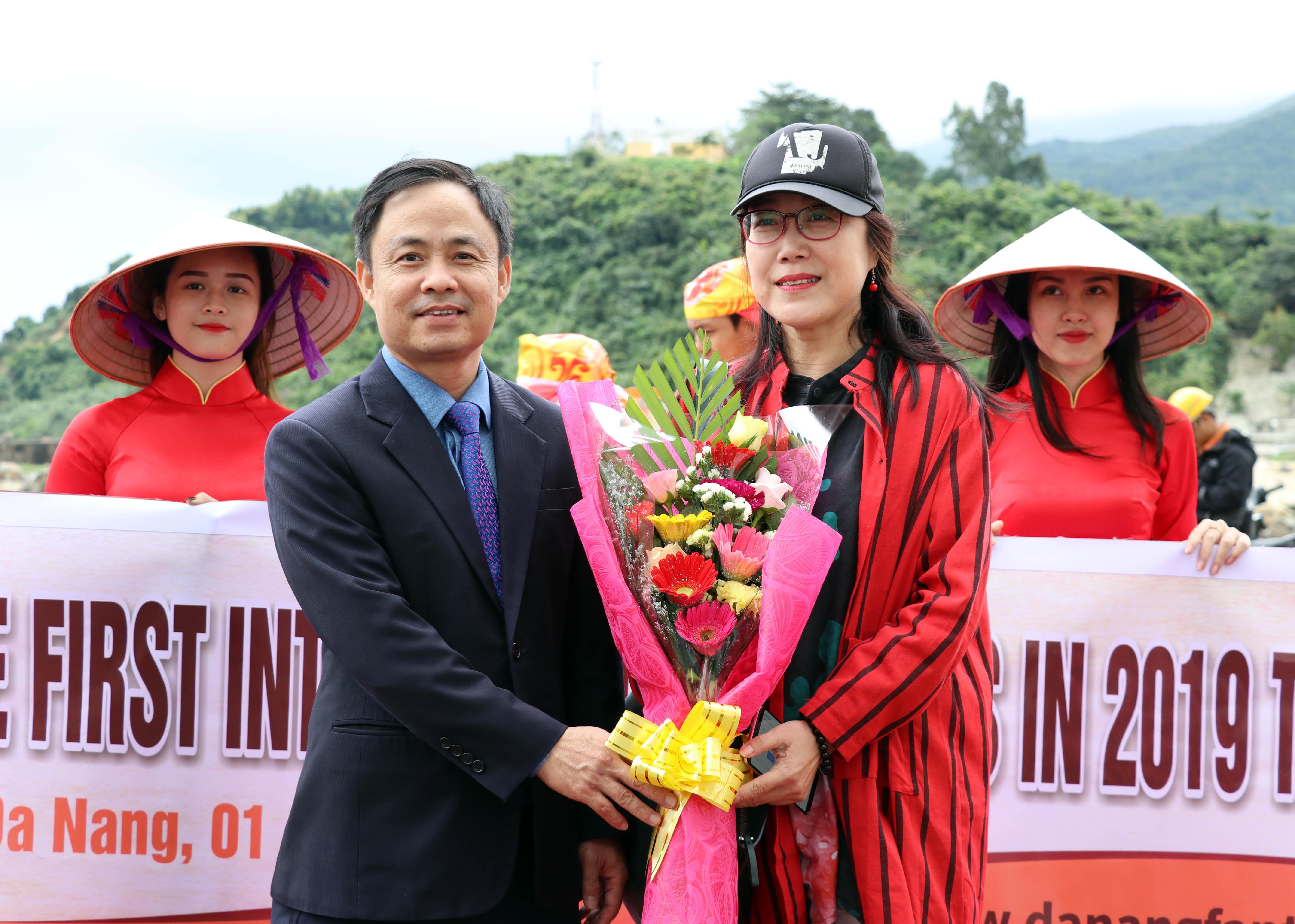 Tặng hoa cho một trong những du khách đầu tiên đặt chân đến Đà Nẵng. X.L