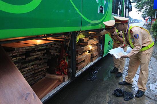 Lực lượng CSGT kiểm tra, xử lý xe khách chở gỗ thành phẩm không có hóa đơn chứng từ vào sáng 12.1. Ảnh: T.C
