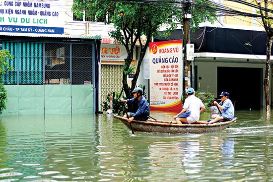 Người dân dùng ghe để di chuyển trên đường Phan Bội Châu - Tam Kỳ trong đợt ngập úng giữa tháng 12.2018.Ảnh: PHƯƠNG THẢO