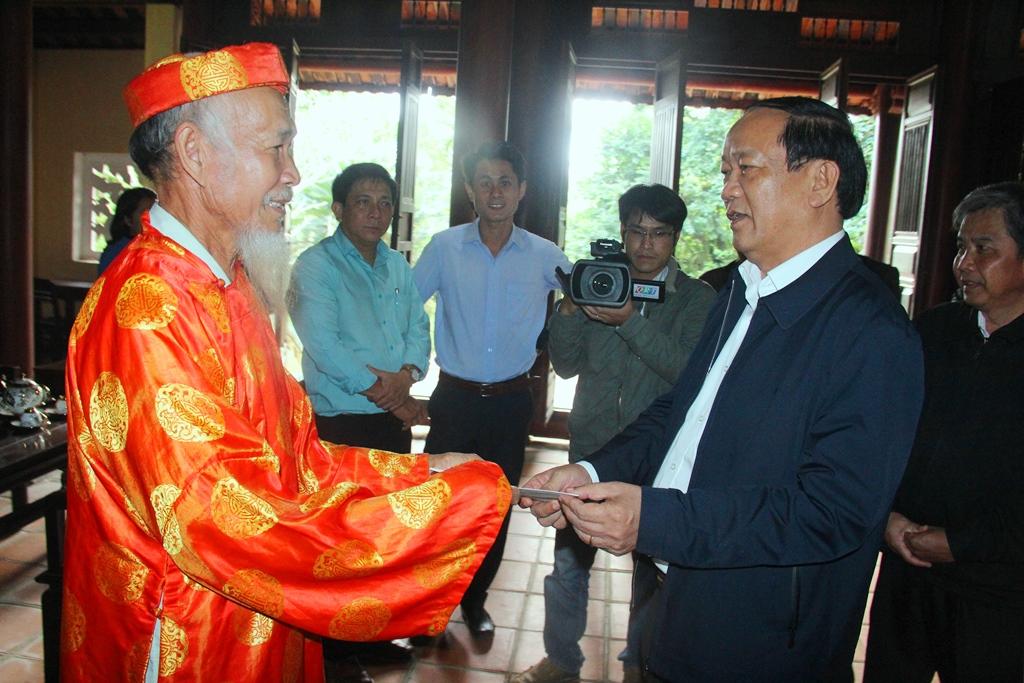 Chủ tịch UBND tỉnh Đinh Văn Thu động viên và trao quà cho ông Phân Ngấu - người trông coi Nhà lưu niệm cụ Phan Châu Trinh. Ảnh: A.N