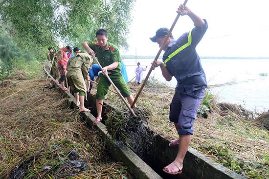 Đoàn thanh niên Công an tỉnh giúp dân dọn dẹp vệ sinh, khai thông kênh mương sau lũ. Ảnh: M.L