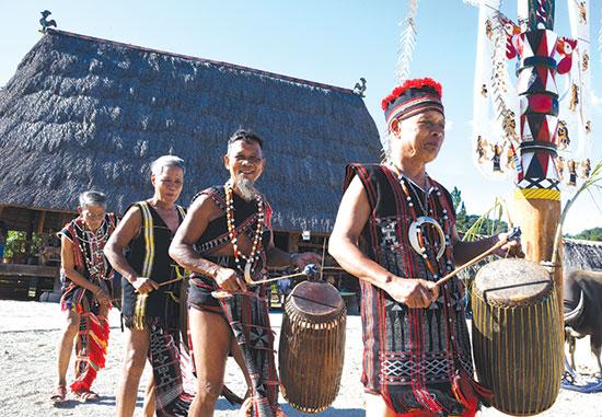 Những nghệ nhân diễn tấu trống chiêng trong lễ hội với món trang sức bằng nanh heo rừng. Ảnh: Tấn Vịnh