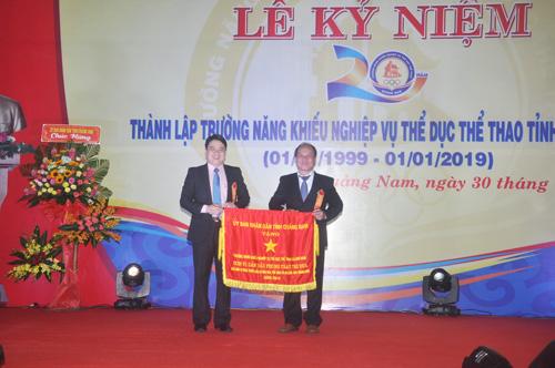 Phó Chủ tịch UBND tỉnh Trần Văn Tân tặng cờ thi đua xuất sắc năm 2018 cho lãnh đạo nhà trường. Ảnh: T.V
