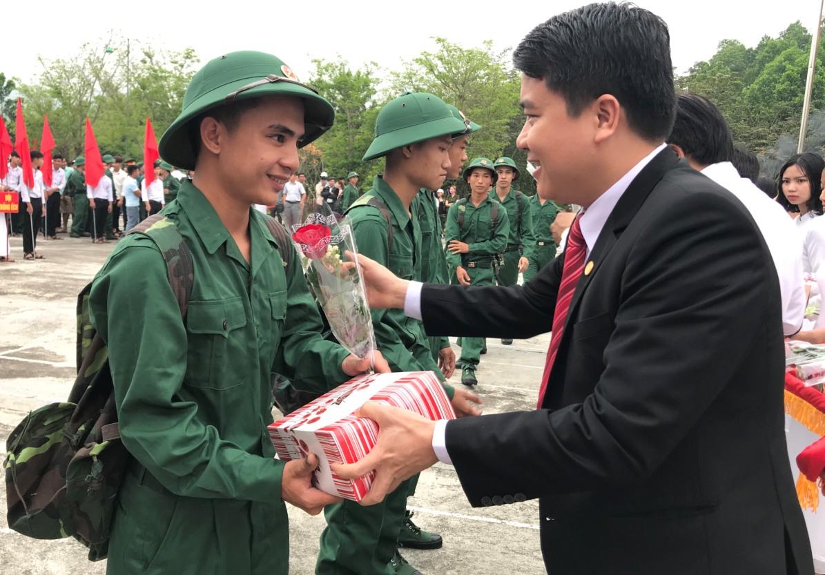 Phó Chủ tịch UBND tỉnh Trần Văn Tân tặng hoa, quà động viên thanh niên huyện Nông Sơn lên đường làm nhập ngũ. Ảnh: VA