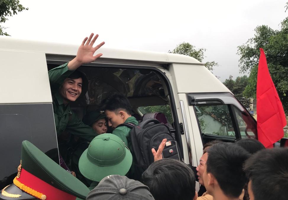 Thanh niên vẫy tay chào bạn bè, người thân lên đường. Ảnh: VA