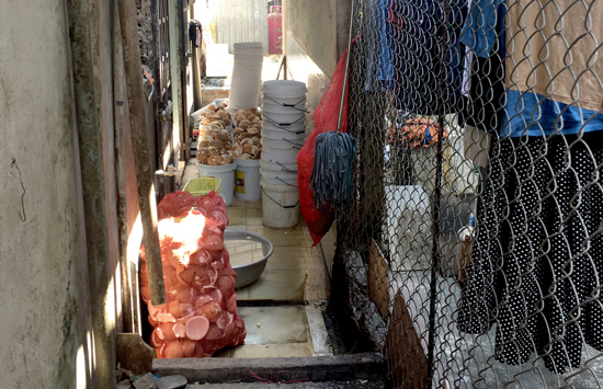 Lối đi chung của khu dân cư bị chắn bởi nhiều đồ phế thải của cơ sở sản xuất bánh dừa nướng. Ảnh: PHAN VINH