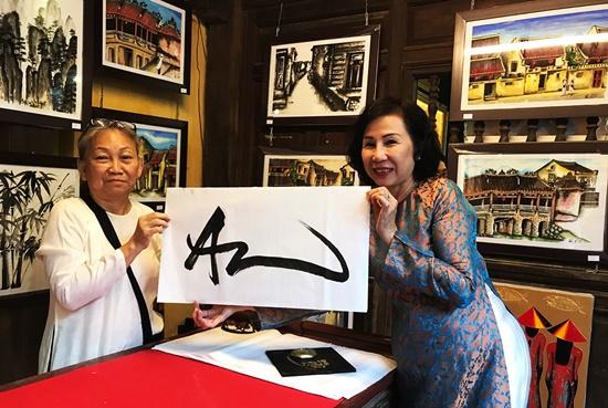 Du khách chụp hỷ niệm với nữ thư pháp Huỳnh Thị Mỹ Lý (trái)