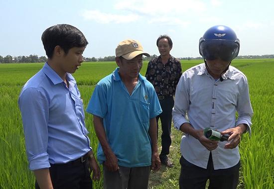 Cán bộ kỹ thuật hướng dẫn nông dân sử dụng thuốc diệt chuột Racumin. Ảnh: Biên Tân