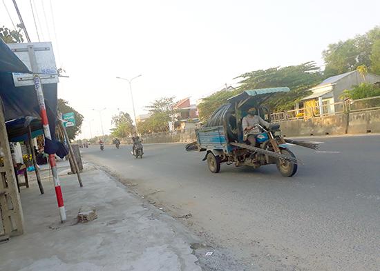 Xe lôi, người tham gia giao thông không đội mũ bảo hiểm trên quốc lộ 1, đoạn qua huyện Thăng Bình. Ảnh: THANH THẮNG