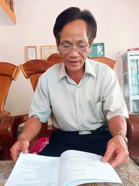 Thầy giáo Huỳnh Ngọc Sáu đọc lại tiểu phẩm do chính mình biên soạn trước khi dàn dựng. Ảnh: T.THU