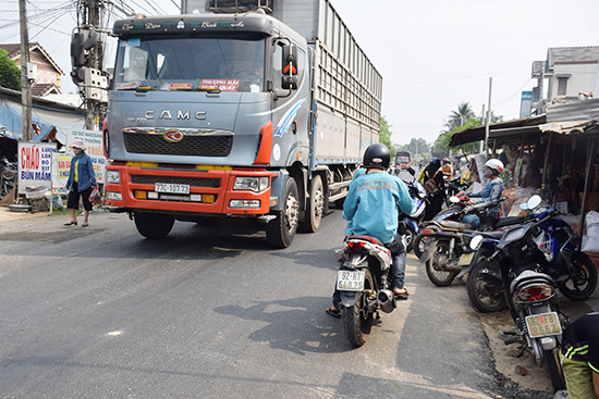 Người dân thường xuyên lấn chiếm lòng đường tuyến QL14E, đoạn qua trước chợ Bình Quý (xã Bình Quý, Thăng Bình) khiến việc lưu thông của các phương tiện gặp khó khăn.Ảnh: THANH THẮNG