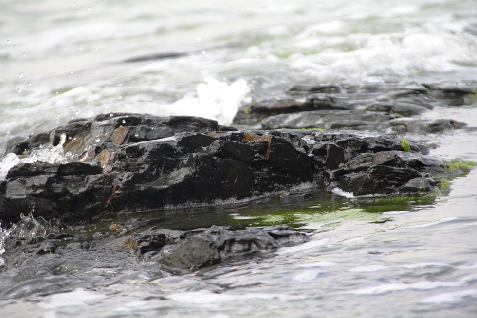 The stone blocks are in pure black, sparkling besides water here.
