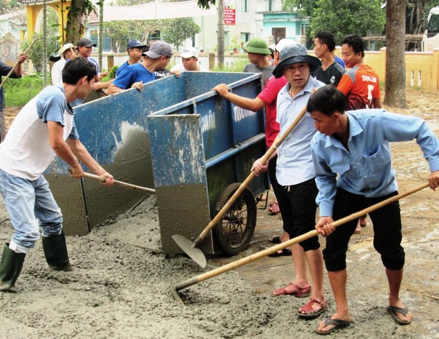 Các bạn đoàn viên tích cực tham gia đổ bê tông sân nhà văn hóa thôn Phú Bông (Duy Trinh, Duy Xuyên). Ảnh: HOÀI NHI