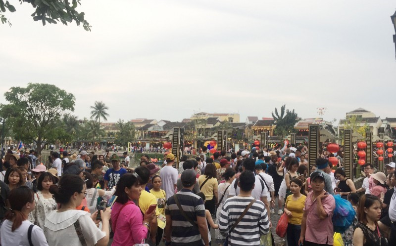 Visitors on the banks of the Hoai river which flows through the ancient quarter of Hoi An city
