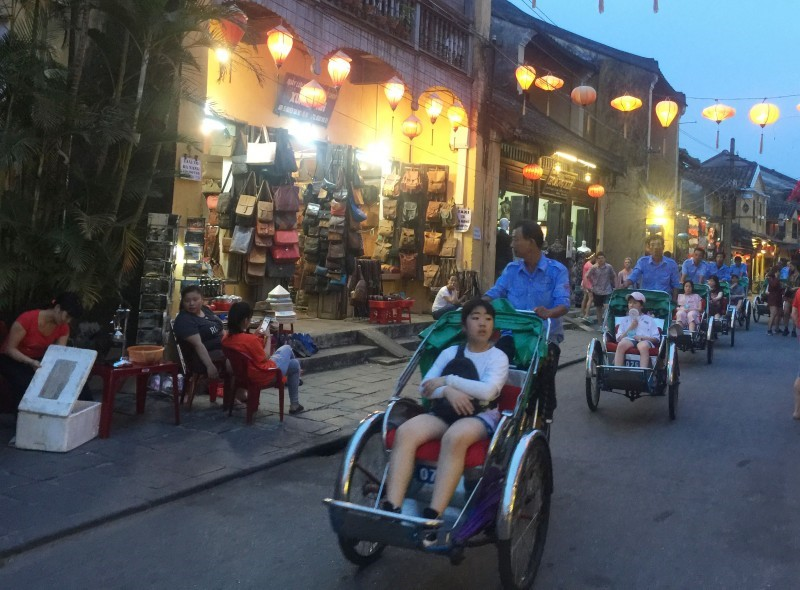Visitors like enjoying Hoi An night with colourful lanterns on pedicabs.