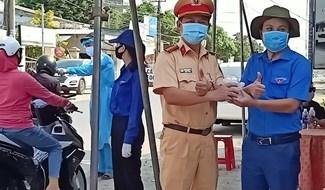 Bí thư Huyện đoàn Đại Lộc - Mai Thanh Sang cùng nhiều đoàn viên, thanh niên phục vụ nước đóng chai, nước giải khát cho cán bộ, chiến sĩ làm nhiệm vụ tại điểm chốt chặn. Ảnh: HOÀNG LIÊN